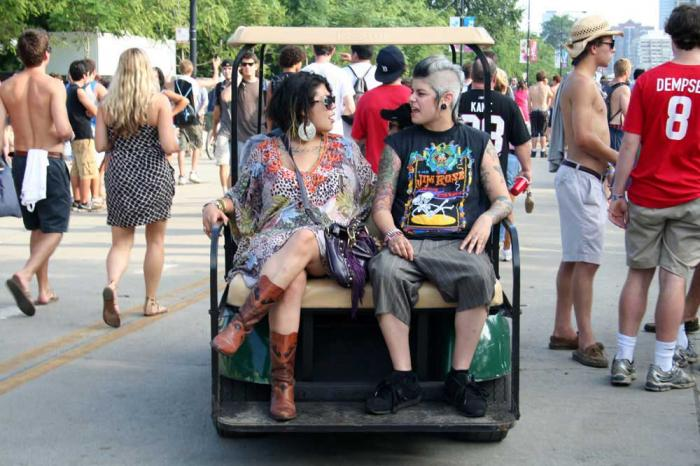Two concert goers riding in a cart at Lollapalooza. Bet they have their Lolla cashless wristbands!